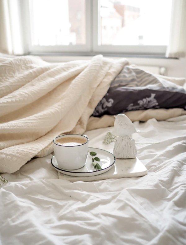 letto con lenzuola stropicciate e tazza di qualcosa tipo caffé