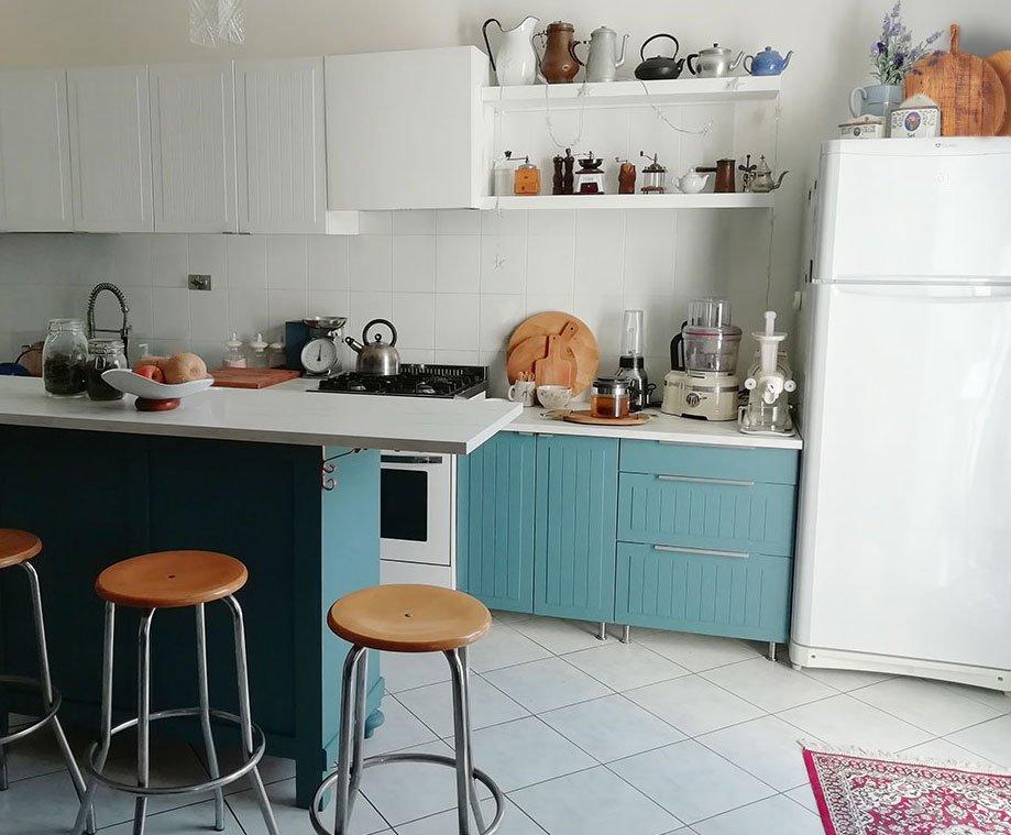 La cucina dopo il rinnovo: sotto blu petrolio, sopra bianca con in più un'isola blu petrolio e sgabelli in acciaio e legno chiaro