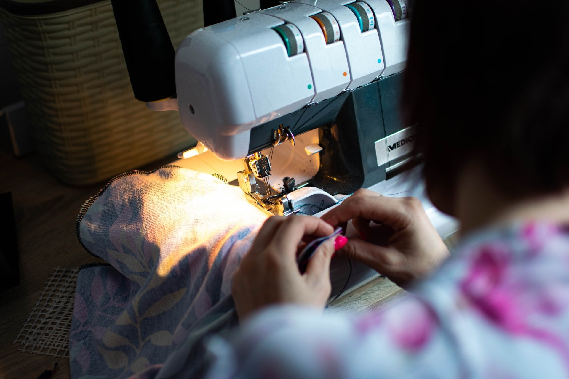 donna che cuce con tagliacuci, autoproduzione abiti