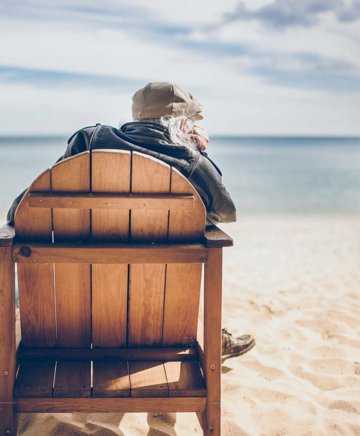 anziano seduto su una sedia in spiaggia
